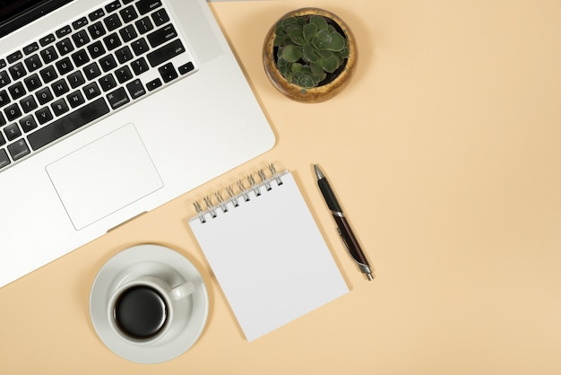 Vista elevada de la computadora portátil; taza de café; bolígrafo; y la libreta espiral sobre fondo beige Foto gratis