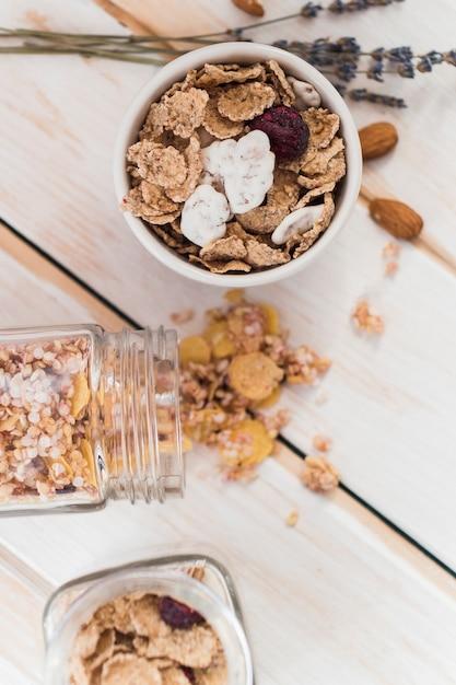 Vista elevada de copos de maíz en un tazón y un frasco derramado de granola sobre fondo de madera Foto gratis
