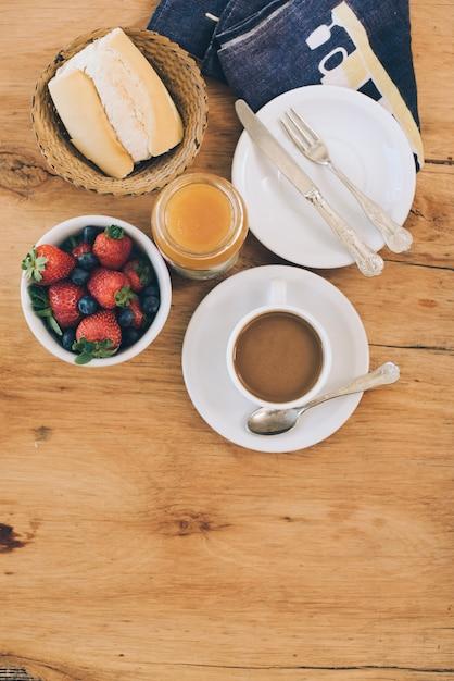 Una vista elevada de desayuno saludable con café en mesa de madera Foto gratis