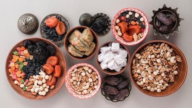 Una vista elevada de dulces tradicionales; frutos secos y nueces sobre fondo blanco Foto gratis