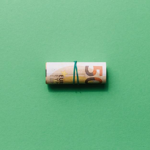 Vista elevada de enrollada nota de cincuenta euros sobre fondo verde Foto gratis