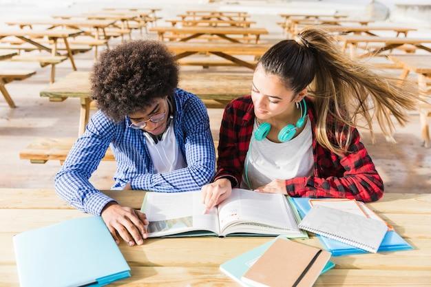 Una vista elevada de estudiantes universitarios leyendo los libros en el aula. Foto gratis