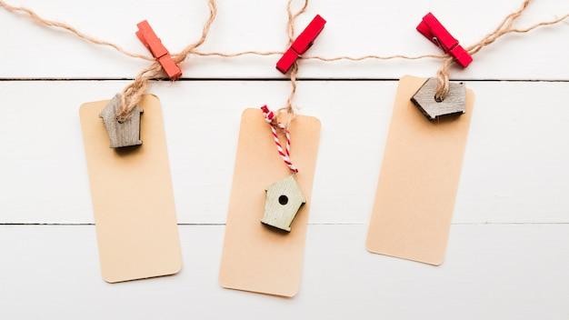 Una vista elevada de la etiqueta de pajarera atada con pinzas de tela en un tablón de madera blanco Foto gratis