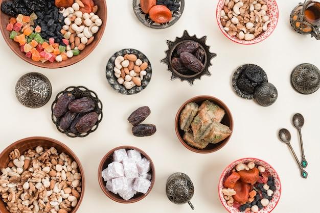 Una vista elevada de frutos secos; nueces; fechas; cuencos de lukum y baklava sobre el fondo blanco Foto gratis