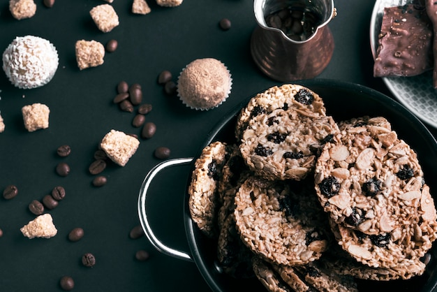 Una vista elevada de galletas en utensilios y granos de café sobre fondo negro Foto gratis