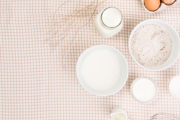 Vista elevada de la harina; leche; azucar y huevo sobre servilleta a cuadros Foto gratis