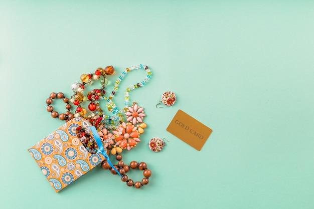 Vista elevada de hermosas perlas accesorios; bolsa de papel y tarjeta de oro sobre fondo verde Foto gratis