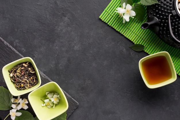 Vista elevada del ingrediente de hierba seca con tetera en superficie negra Foto gratis