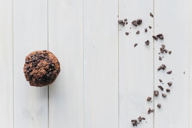 Vista elevada de la magdalena con chip de chocolate y chocolate esparcido sobre fondo de madera Foto gratis