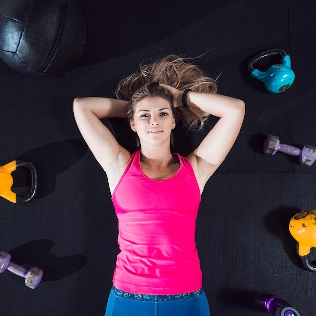 Vista elevada de una mujer joven tendida en el suelo rodeada de equipos de ejercicio Foto gratis