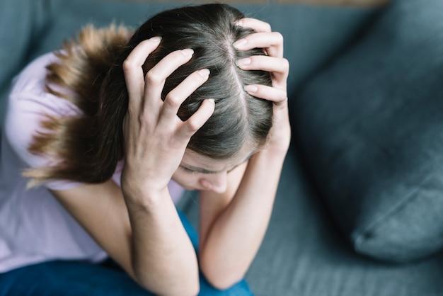 Vista elevada de una mujer que sufre de dolor de cabeza. Foto gratis