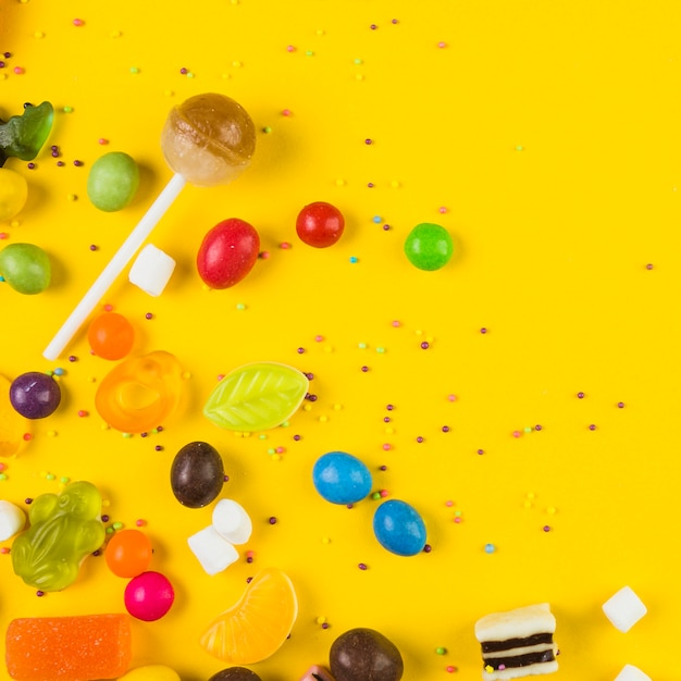 Vista elevada de paleta y caramelos sobre fondo amarillo Foto gratis