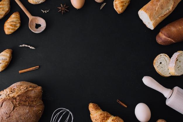 Vista elevada de panes; utensilios de cocina huevo y especias formando marco sobre fondo negro Foto gratis