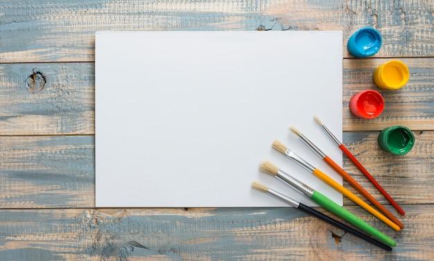 Vista elevada de papel blanco con pequeños contenedores de acuarela y pinceles en madera con textura Foto gratis