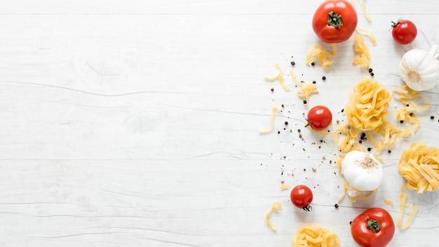Vista elevada de pasta cruda de tallarines crudos con tomate; ajo y pimienta negra sobre tabla blanca. Foto gratis