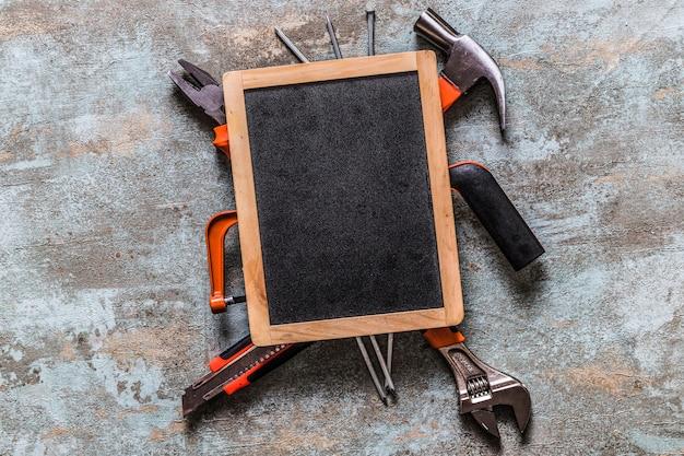 Vista elevada de la pizarra en blanco sobre varias herramientas de trabajo Foto gratis