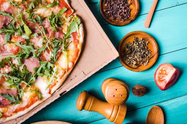 Vista elevada de la pizza italiana del tocino con las hierbas; rodaja de tomate dientes y peppermill sobre fondo turquesa. Foto gratis