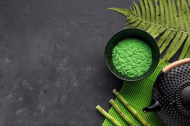 Vista elevada de polvo de té matcha verde con hojas de helecho y palo de bambú en superficie negra Foto gratis
