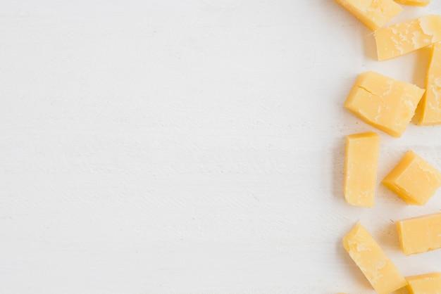 Una vista elevada de las rebanadas de queso cheddar sobre fondo blanco Foto gratis
