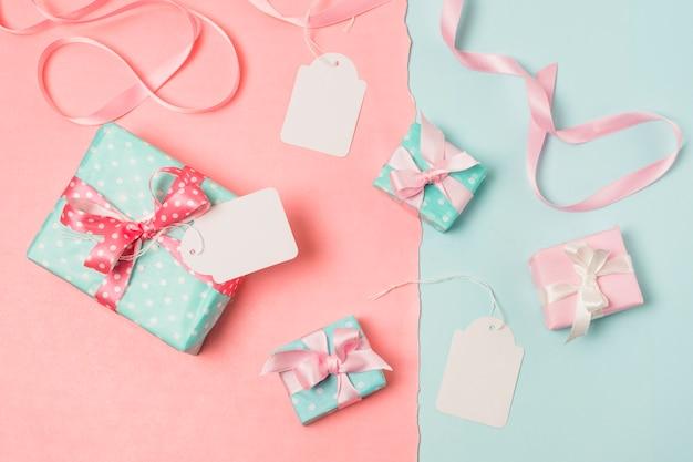 Vista elevada de regalos; etiquetas en blanco y cinta Foto gratis