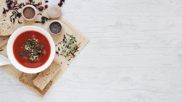 Vista elevada de sopa e ingredientes en mantel contra mesa de madera Foto gratis