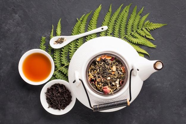 Vista elevada de té de hierbas e ingredientes saludables con hojas de helecho sobre fondo negro de pizarra Foto gratis