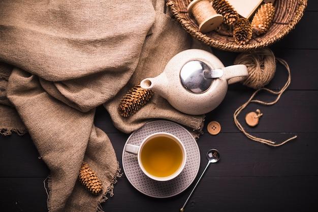 Vista elevada de té de hierbas; piña; tetera; saco; botón; cesta de mimbre y ovillo de hilo en mesa. Foto gratis