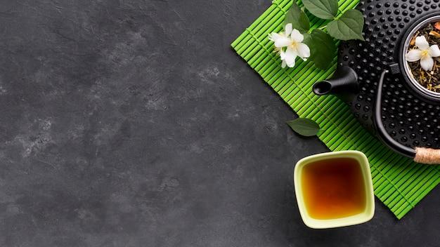 Vista elevada del té de hierbas y su ingrediente en superficie texturada negra Foto gratis