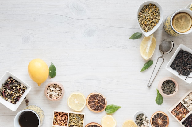 Vista elevada de té de limón; hierbas; colador; crisantemo chino seco y pomelo seco. Foto gratis