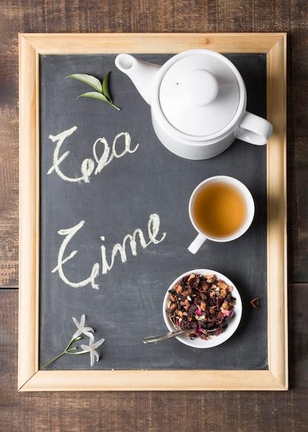 Una vista elevada de la tetera; taza de té de limón y hierbas secas con hojas y flores en la pizarra Foto gratis