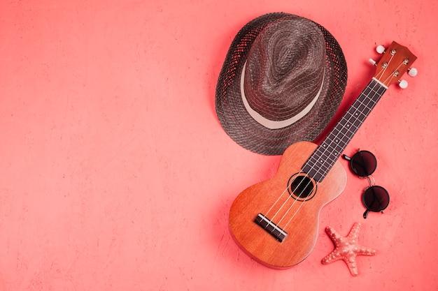 Una vista elevada del ukelele; gafas de sol; estrella de mar y sombrero sobre fondo coral Foto gratis