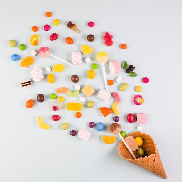 Vista elevada de varios caramelos con cono de waffle de helado sobre fondo blanco Foto gratis