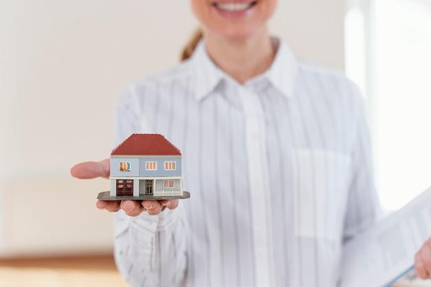 Vista frontal del agente inmobiliario femenino defocused sonriente que muestra la casa en miniatura Foto gratis