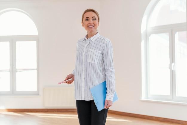 Vista frontal del agente inmobiliario femenino sonriente en casa vacía Foto gratis