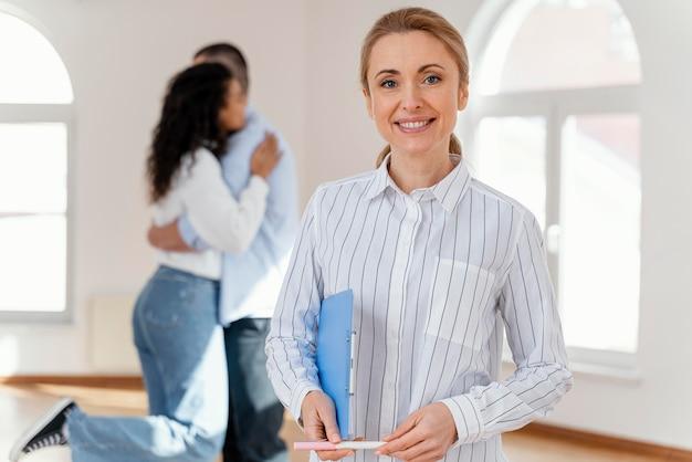 Vista frontal del agente inmobiliario femenino sonriente con la joven pareja abrazándose en el fondo Foto gratis