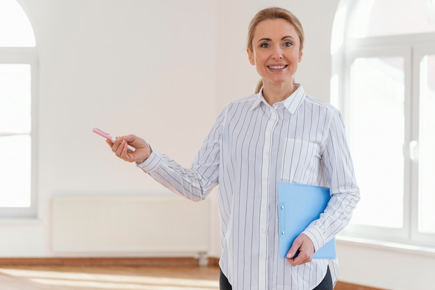 Vista frontal del agente inmobiliario femenino sonriente con portapapeles en casa vacía Foto gratis