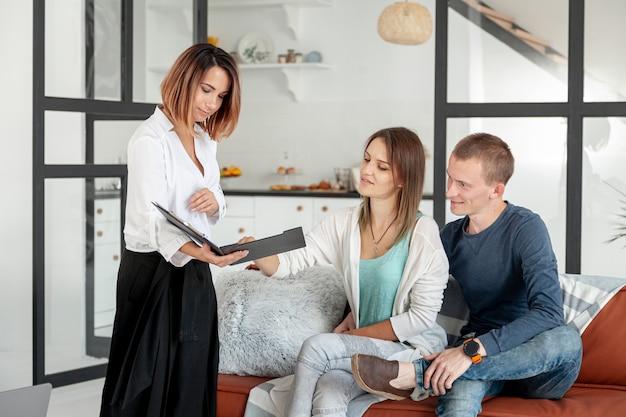 Vista frontal agente inmobiliario hablando con hombre y mujer Foto Premium