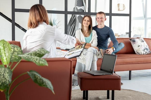 Vista frontal agente inmobiliario hablando con pareja Foto gratis