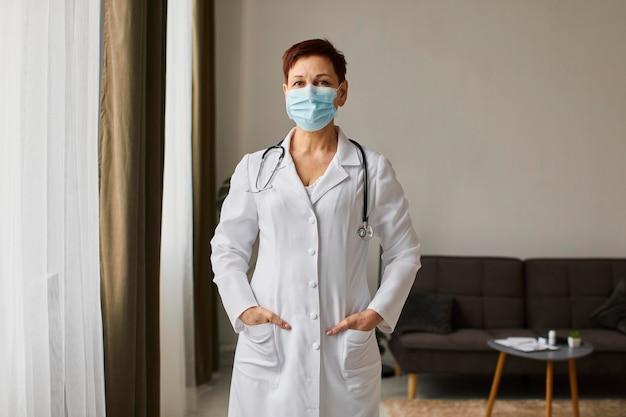 Vista frontal de la anciana doctora del centro de recuperación de covid con máscara médica Foto gratis