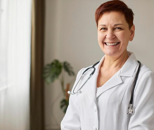 Vista frontal de la anciana sonriente doctora del centro de recuperación covid Foto gratis