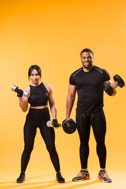 Vista frontal de atletas con pesas Foto gratis