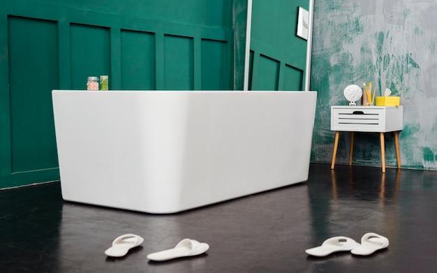 Vista frontal del baño con espejo y zapatillas. Foto gratis