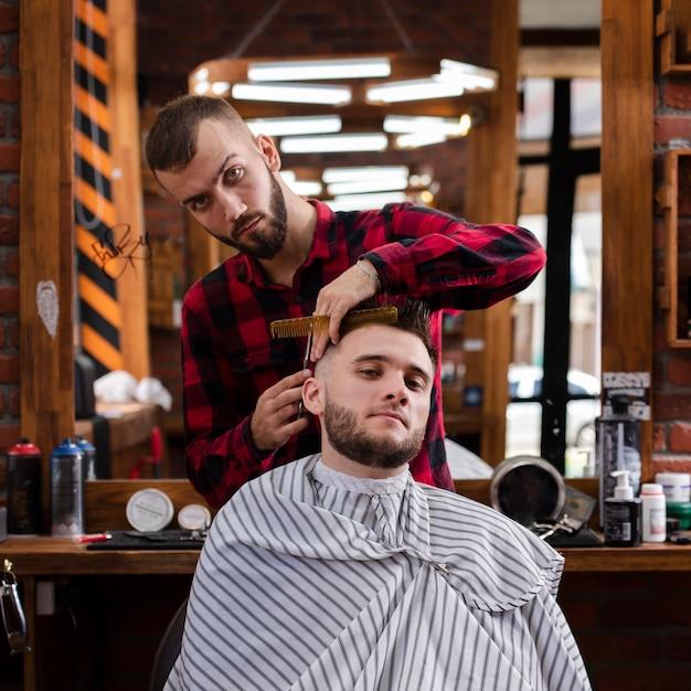 Vista frontal barbero midiendo cabello Foto gratis