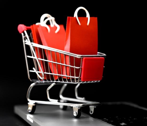 Vista frontal de las bolsas de la compra en el carro para el cyber monday Foto gratis