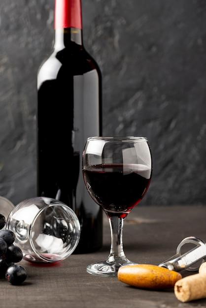 Vista frontal botella de vino tinto y vasos Foto gratis