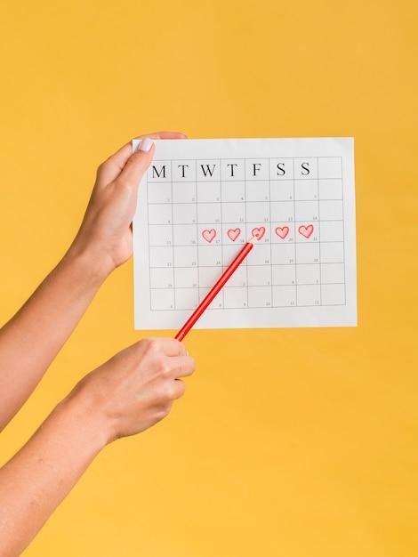 Vista frontal del calendario de menstruación con corazones y un lápiz Foto gratis