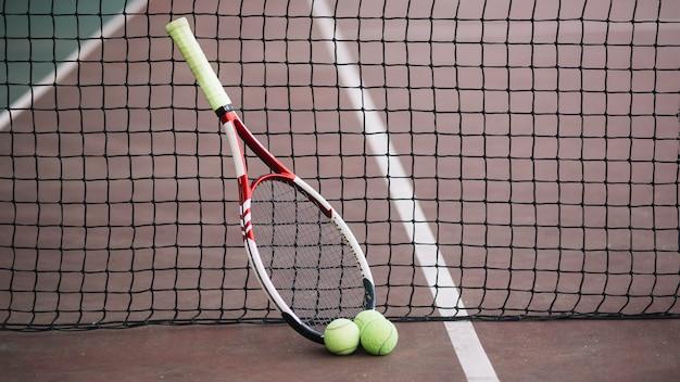 Vista frontal del campo de juego de tenis con raqueta Foto gratis