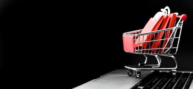 Vista frontal del carrito de compras de cyber monday con bolsas y espacio de copia Foto gratis