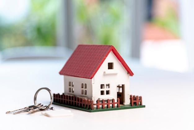 Vista frontal de la casa modelo de juguete y llaves en el fondo borroso Foto gratis