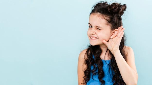 Vista frontal chica recogiendo con pose de oreja Foto gratis